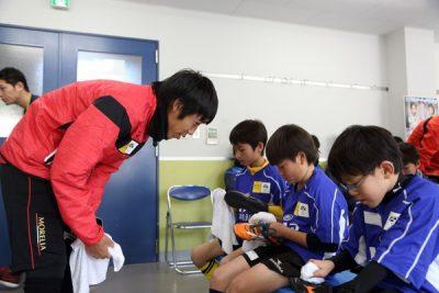 スパイク磨きをする選手とコミュニケーションをとる中村憲剛選手